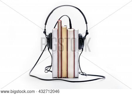 Stack Of Books With The Earphones Isolated On White Background. Audiobooks. Listen And Study Concept