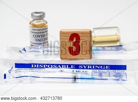 Booster Shot For Mrna Vaccines For Covid-19 With Wooden Block With Number Three With Disposable Syri