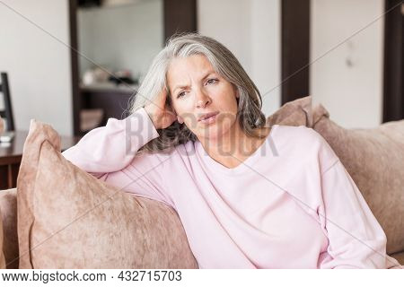 Sad pensive middle age woman looking down depressed sitting on the sofa in the living room at home. Gray-haired female sitting on couch