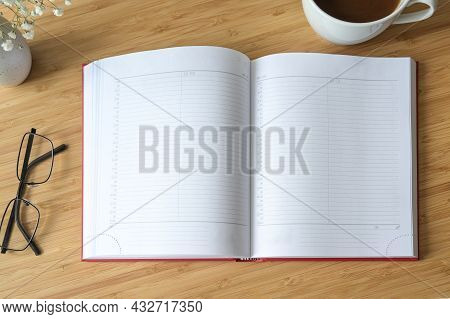 Flat Lay Mock-up Of A Blank Open Diary Or Appointment Calendar On A Wooden Desk With Coffee And Glas