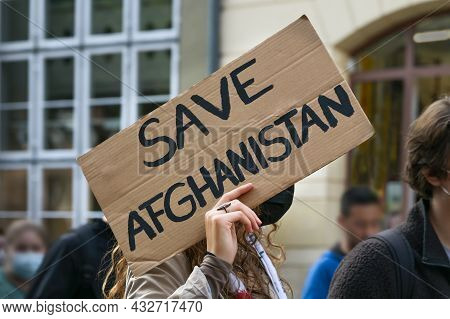 Female Activist Holding A Cardboard Sign With Text Safe Afghanistan At A Demonstration In Lubeck, Ge