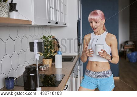 Young Woman Shows Jar Of Dietary Supplement Recording New Video In Kitchen