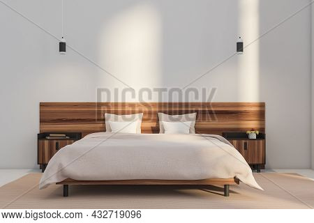 Bedroom Interior With Two On Trend Pendant Lights Over A Wood Bed With A Big Headboard. Beige Sheet-