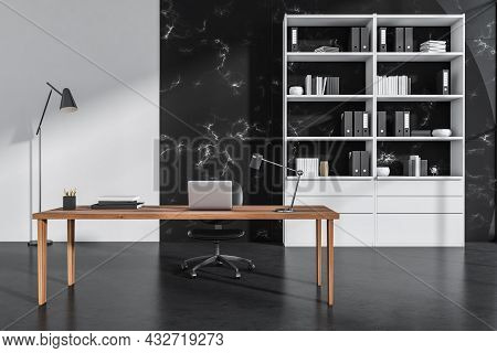 Close View On Dark Office Room Interior With Laptop, Comfortable Armchair, Desk, Books, Folders, Boo