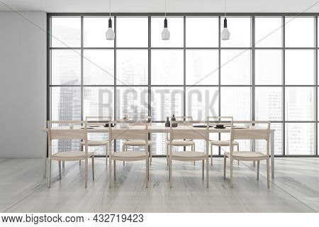 Dining Room Interior With A Panoramic View, Three Pendant Lights, A Light Wood Table With Eight Chai
