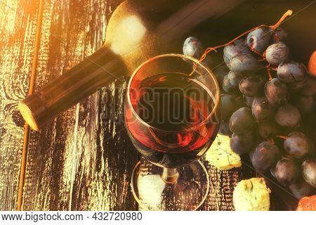 Dusty Bottle Of Wine On The Old Wooden Background Sunbeams