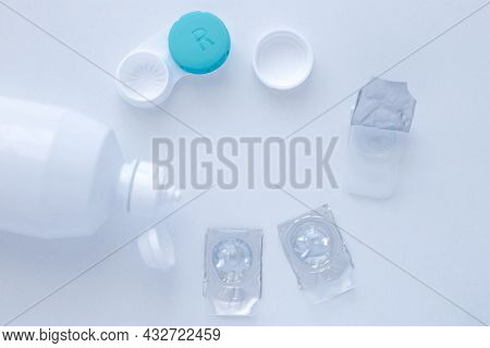 Lens Remover, A Container For Storing Lenses And Two Contact Lenses Lie On The Sides On A White Back