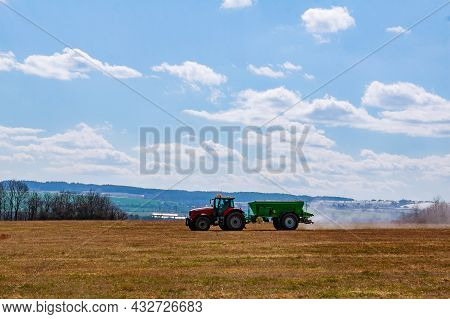 A Red Tractor With A Green Trailer Spreads Granular Fertilizer On The Ground In The Field. Soil Prep