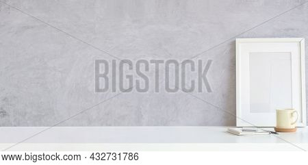 Blank Poster Frame And Coffee Cup On White Table With Cement Wall.copy Space For Products Display Mo
