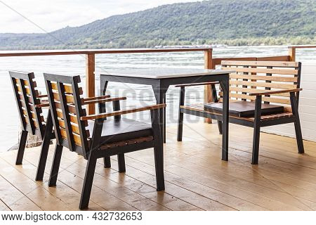 Empty Brown Wooden Dining Table Set At Seaside Terrace