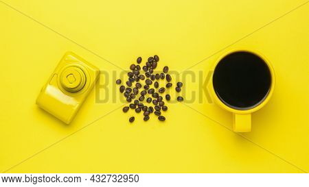 A Yellow Camera, A Yellow Cup Of Coffee And Coffee Beans On A Yellow Background. A Popular Hot Drink