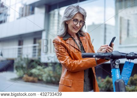 Smiling Mature Woman Uses Phone Standing Near E-scooter Exposed On City Street