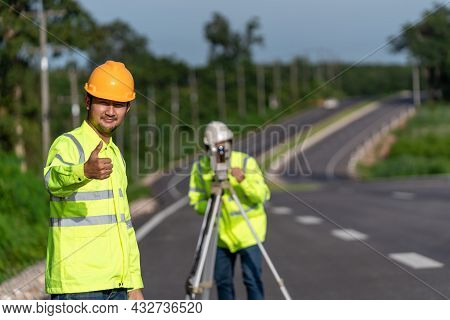 Asian Happy Surveyor Engineers With Digital Level Looking At Camera On Road Construction Site, Civil