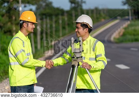 Two Surveyor Engineers Worker Handshake After Making Measuring With Theodolite Instrument Equipment