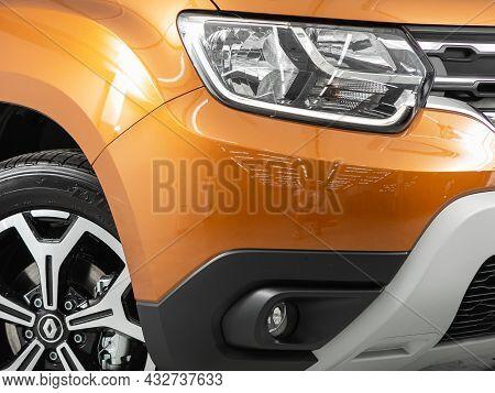Novosibirsk, Russia - August 19, 2021: Orange  Renault Duster, Red Car Xenon Lamp Headlight, Bumper,