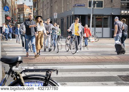 Amsterdam-netherlands - August 21 2017; People Crossing City Street Including Woman In Black Hat And