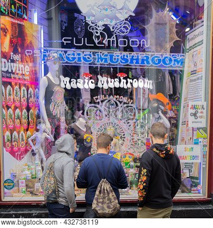 Amsterdam-netherlands - August 21 2017;three Young Male Tourists Standing At Window Of Shop Selling