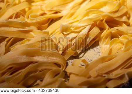 Close Up Of Homemade Fresh Tagliatelle Pasta In Bright Yellow Shade