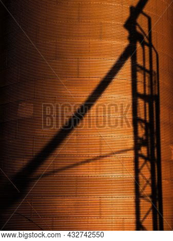 Several tall steel grain silos for storing crops and shadow of stairs