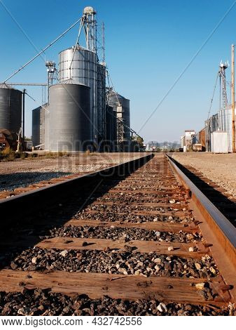 Several tall steel grain silos for storing crops and blue sky with railroad tracks for transport