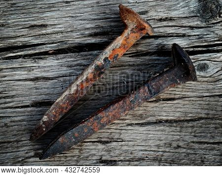 Old rusted iron steel railroad spikes on wood surface