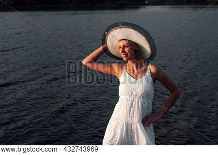 A Young Woman In A Hat Smiles. A Beautiful Happy Blonde In A White Summer Dress Stands In The Water