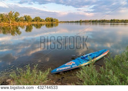 Fort Collins, CO, USA - July 2, 2018: A racing stand up paddleboard by Starboard with a paddle and safety leash on a shore of a calm lake in Colorado after morning workout.