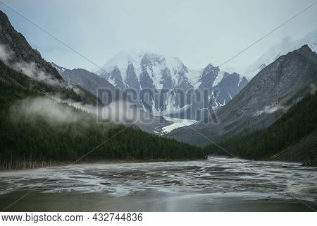 Atmospheric Alpine Landscape With Mountain Lake With Streams From Snowy Mountains In Overcast Weathe