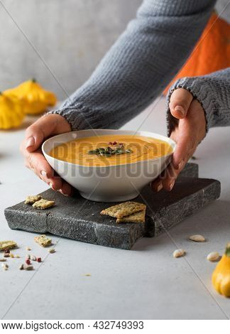 A Bowl Of Warm Pumpkin Soup With Seeds In Your Hands. Comfortable Riding. Vegetarian Dishes.