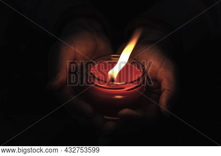 Close-up Of Hands Holding A Burning Candle In The Dark. Adult Woman With A Red Candle Against A Blac