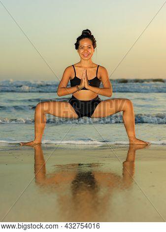 Beach Yoga Practice. Young Woman Practicing Utkata Konasana, Goddess Pose. Hands In Namaste Mudra. O