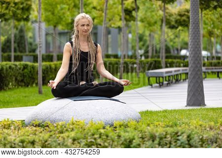 Young Beautiful Woman With Blonde Hair Doing Yoga Exercise In Green Public Park In Summer Morning, O