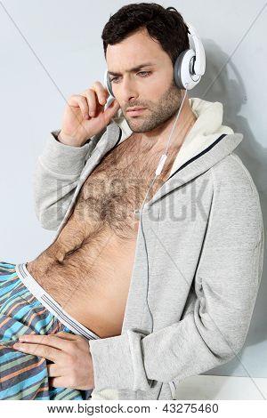 Stijlvolle man luisteren naar muziek op een grijze achtergrond