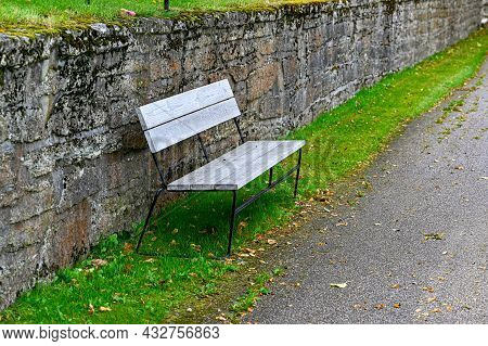 Stonewall And Bench Near A Walkingpath At Cemetery