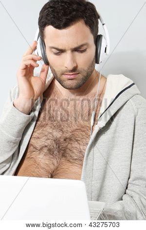 Stijlvolle man in hoofdtelefoon met laptop op een grijze achtergrond