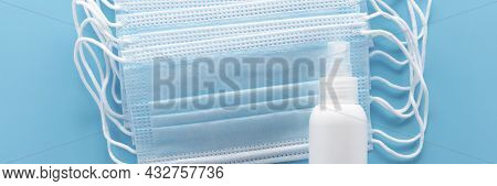 Medical Masks And Spray For Hand Treatment On A Blue Medical Background. Banner. The Concept Of Wear
