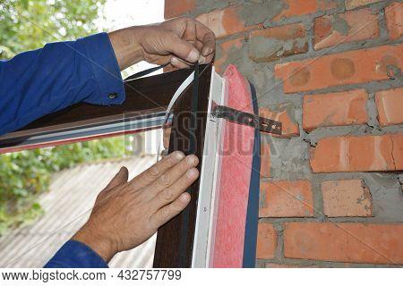 Upvc Window Installation. A Man Is Installing A Self Adhesive Rubber Window Seal Strip, Foam Tape, O
