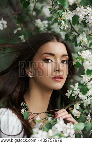 Portrait Of A Woman In The Branches Of A Blooming Apple Tree. Beautiful Natural Makeup