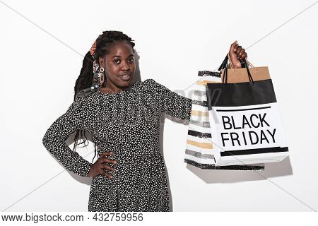 Portrait Of African Elegant Woman In Dress Buying Purchases During Black Friday Isolated On White Ba