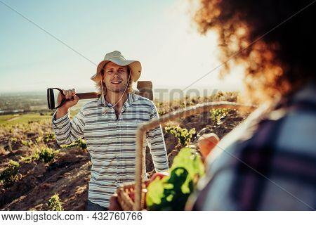 Caucasian Male Farm Worker Holding Shovel Talking To Female Co Worker Standing On Farmlands