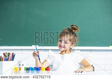 Funny School Girl Pupil Drawing A Picture. Cute Little Preschooler Child Drawing At School.