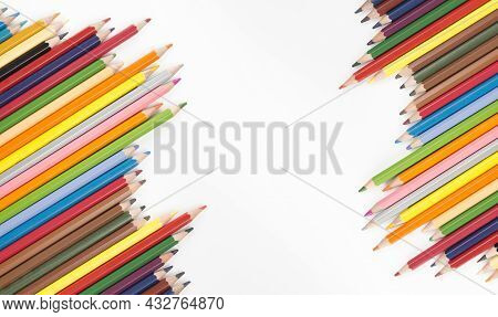 Colored Pencils And Crayon Arranged On White Background