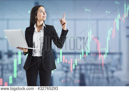 Attractive Young European Businesswoman With Laptop Pointing Up At Creative Glowing Forex Chart Inte