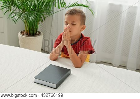Cute Little Boy With Hands Clasped Together Saying Prayer Over Bible At Home