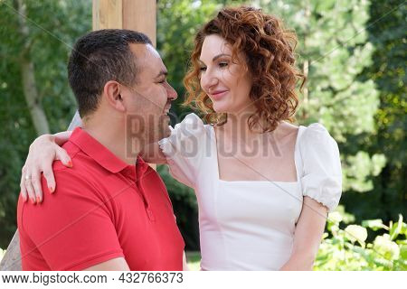 Loving Couple On A Park Bench Look At Each Other With Tenderness. Man In A Red T-shirt And A Curly W