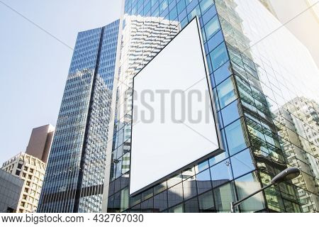 Blank White Billboard On Glass Building In City With Bright Sky And Daylight. Advertisement And Comm