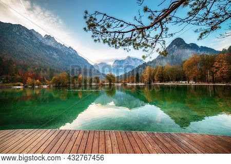 Jasna Lake With Beautiful Reflections Of The Mountains And Wooden Pier. Triglav National Park, Slove