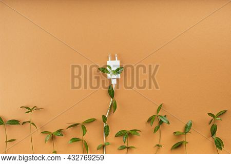 Creative Composition Sprouts Of Green Leaves Germinate In An Electric Plug On A Brown Background. Sa