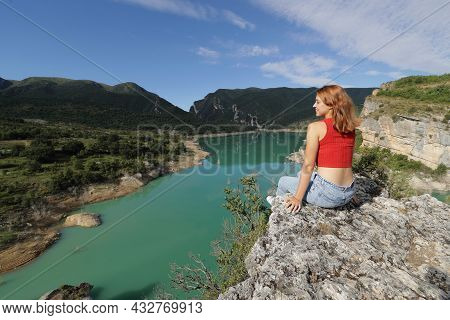 Happy Woman In Red Contemplating Views Of A Lake In The Top Of A Cliff In The Mountain