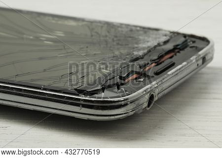Smartphone With Cracked Screen On Light Beige Wooden Background, Closeup. Device Repair